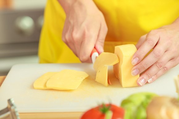 Close Up of Woman Slicing Cheese