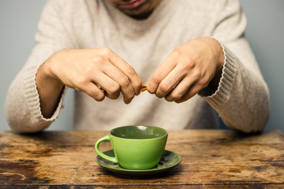 Man Pouring Sweetener Into Cup