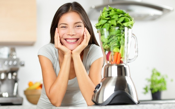 Smiling Woman with Veggies in Blender