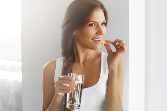 Young Woman With Fish Oil and Glass of Water, Horizontal