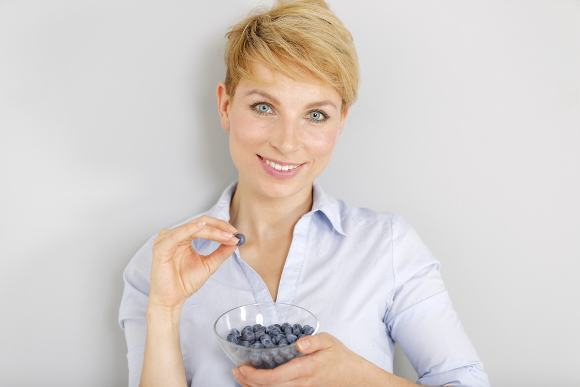 Blonde Woman Eating Blueberries