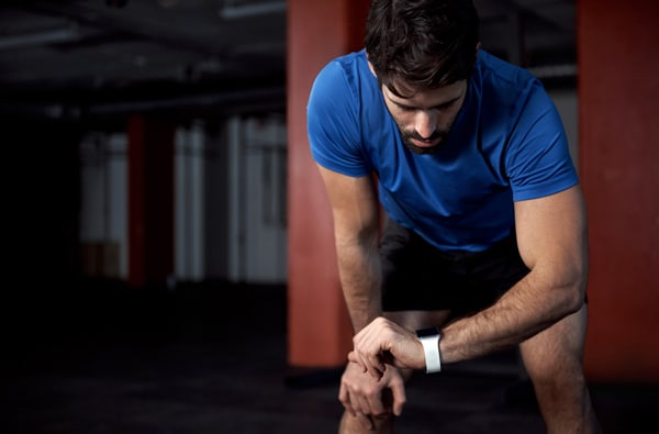 Man Looking at His Watch While Working Out