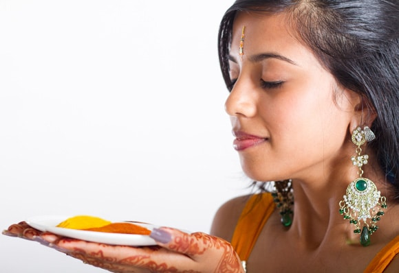 Young Indian Woman Holding a Plate With Turmeric